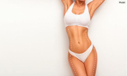 A woman enjoying her slimmed and toned body contours after having liposuction on her abdomen and underarms.