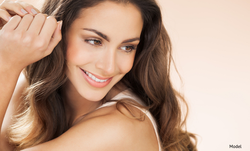 Smiling woman with smooth skin and a defined chin such as the results possible with FaceTite®.