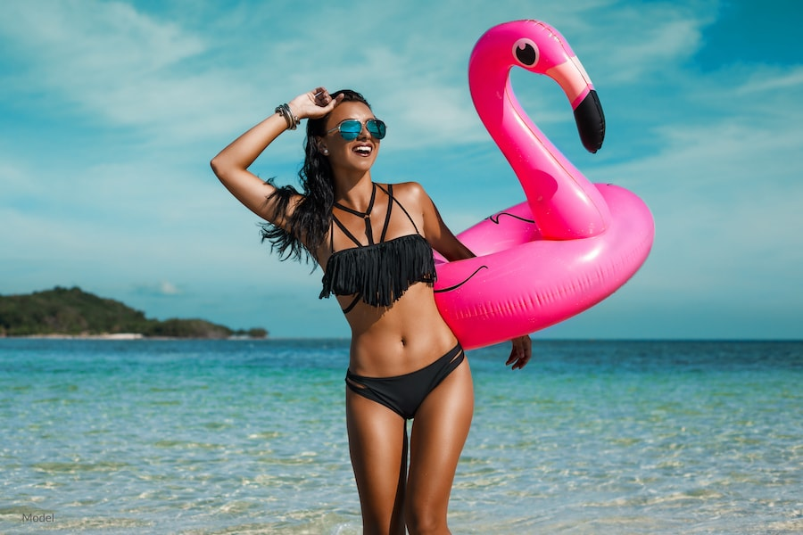 Healthy woman standing on the beach after with a flamingo float.
